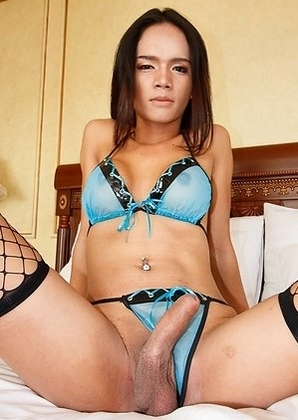 Sexy ladyboy Nan stands with her back to the mirror in a sheer blue and black bikini with stockings. She opens up her top to let out her nice round ti