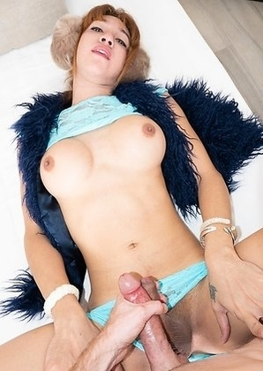Ladyboy Nanny is sitting in a rocking chair wearing a blue fur vest, earmuffs, and heels over a tight blue sheer two-piece.