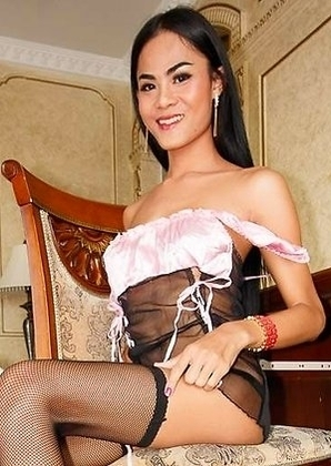 Pretty Poy is dressed in a delicate pink and black lingerie with black stockings and heels. She is sitting at the desk with her legs spread.