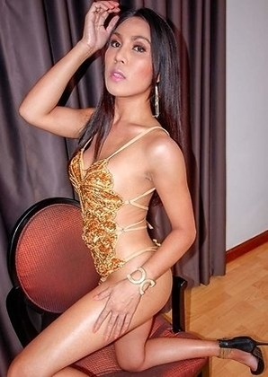 Ladyboy Emmy is wearing a gold dress and high heels. She does a little strip show for the POV on a chair and then lies on the bed.